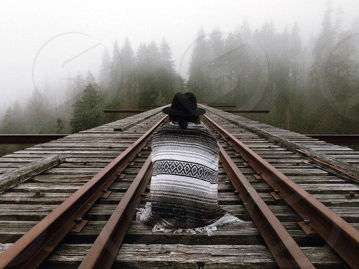 person in black hat with grey and white scarf sitting on train tracks photo