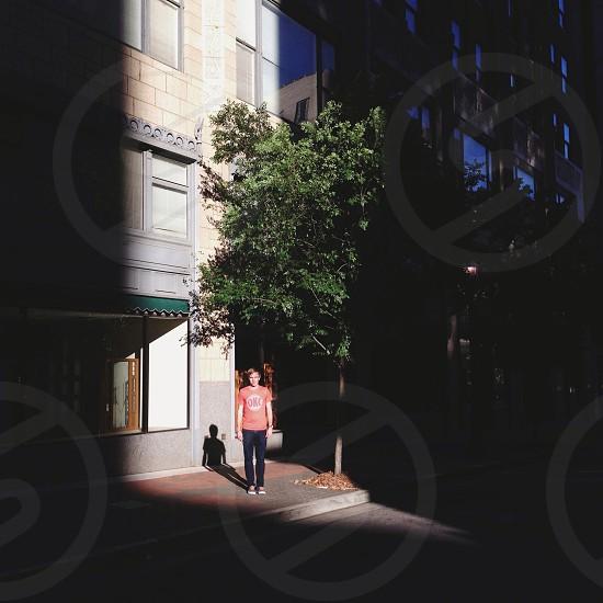 man in orange tshirt in stripe of sunlight in city photo