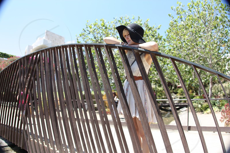 woman in white dress standing and leaning on black metal railings photo