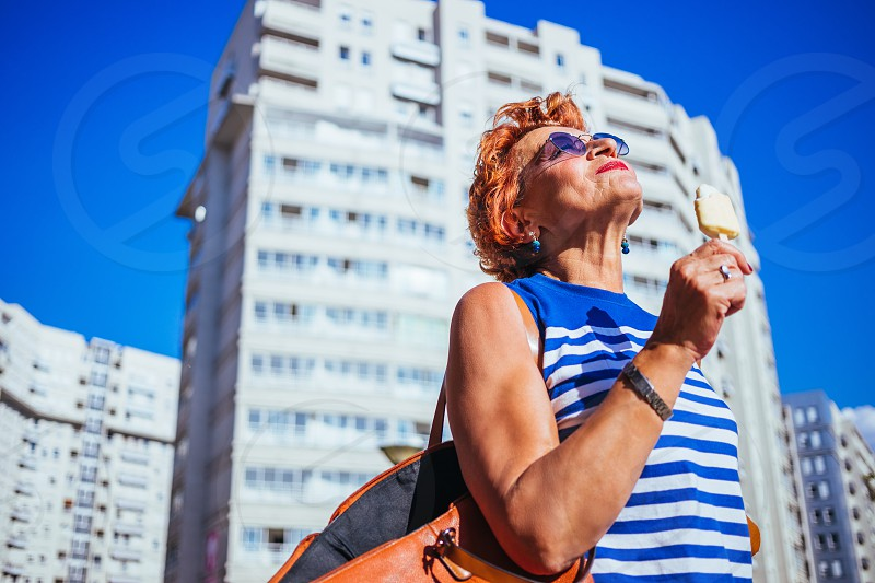 Mature woman eating ice cream on a sunny hot day  photo