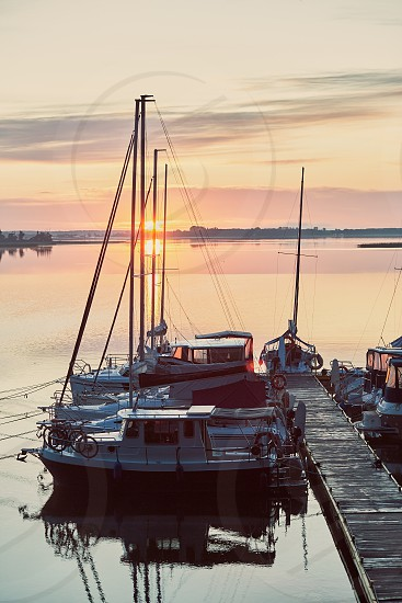 Yachts and boats moored in a harbour at sunrise. Candid people real moments authentic situations photo