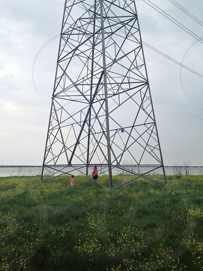 man wearing red shirt under electric tower photo