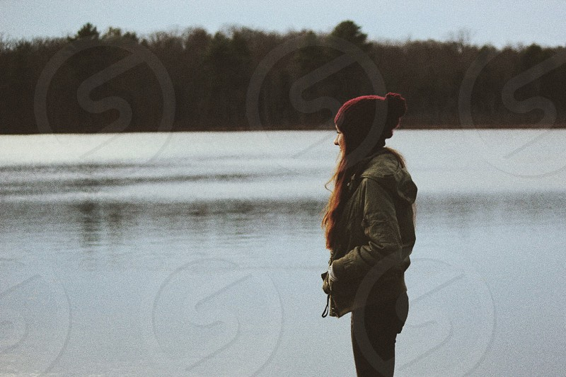woman wearing grey jacket and red knit cap standing near body of water under blue sky during daytime photo