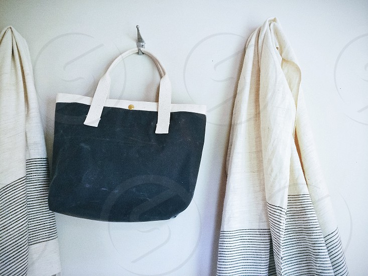 black tote bag hanging on a wall hook photo