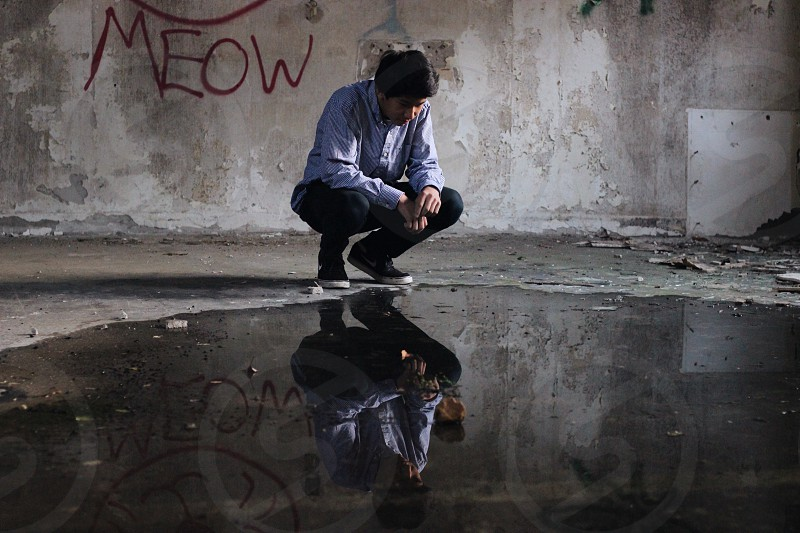 man kneeling over large puddle in abandoned building photo