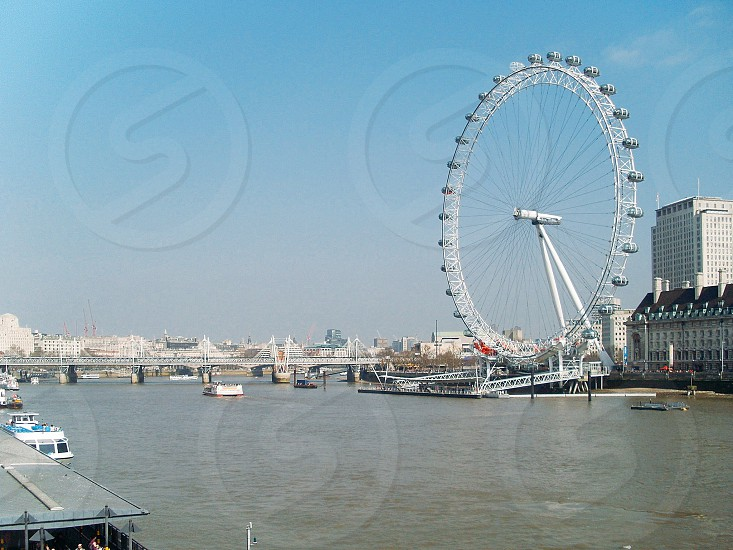feeris wheel beside body of water with bow riders and bridge under blue sky photo
