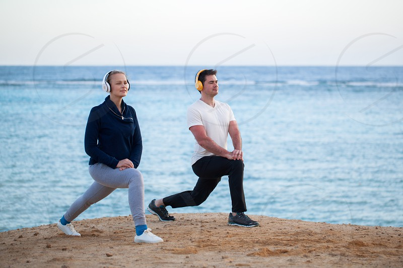 Young man and woman working out together on the beach by the sea. They exercising and listening to music in wireless headphones photo