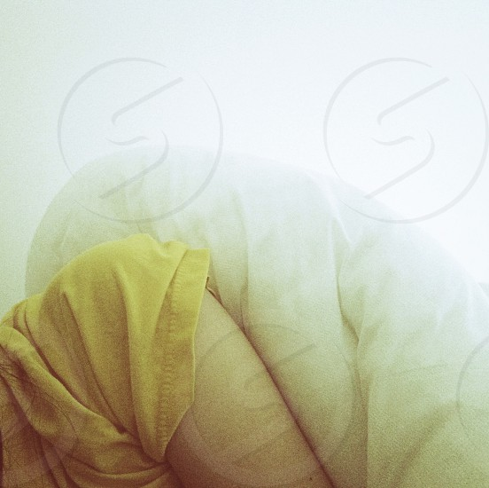 person laying with white linen on top photo