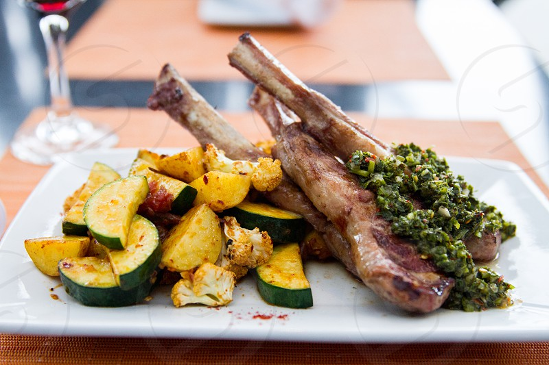 spare ribs and spinach garnished with sliced zucchini on white ceramic rectangular pate photo
