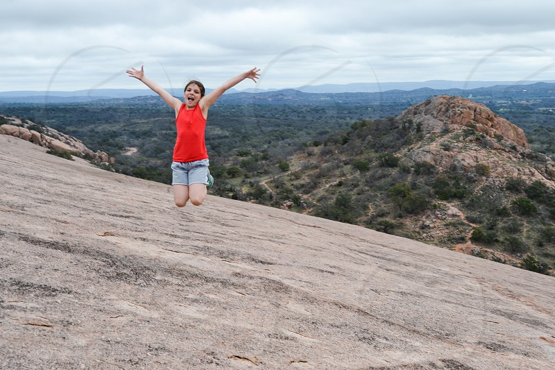 woman jumping spread both arms on rocky mountain photo