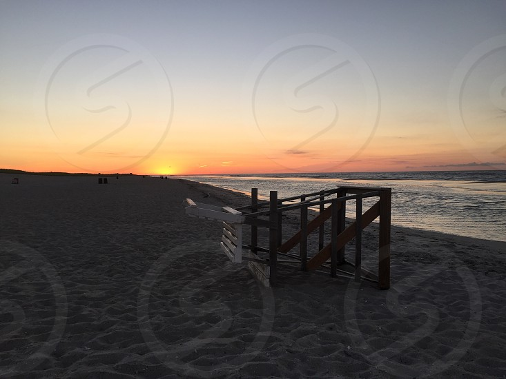 brown wooden frame on sand on seaside during sunrise photo