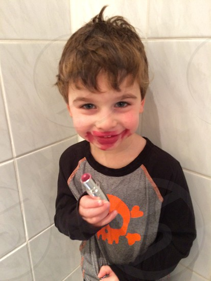 boy in black and gray long sleeve shirt using red lipstick photo