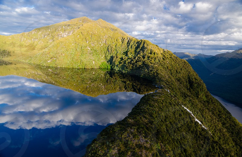 A perfectly still lake high above the fiords below - photographed from a helicopter in Fiordland National Park New Zealand  photo