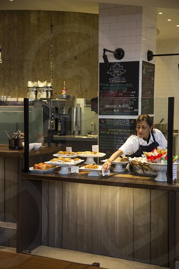 woman in white polo shirt and black apron arranging pastries on display photo