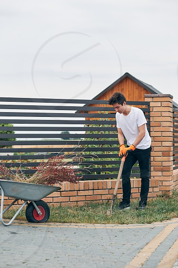 Teenage boy planting the plants working at a home garden. Candid people real moments authentic situations photo