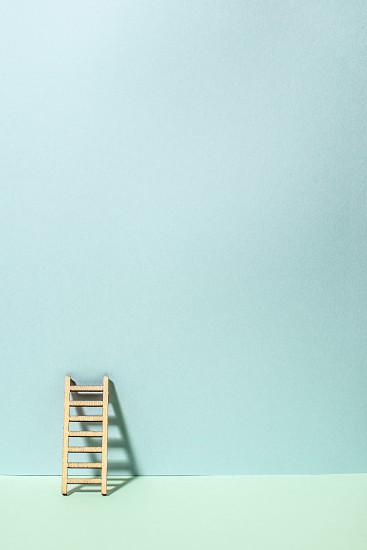 Wooden ladder on wall. Pastel tones. Concept for success and growth. Business metaphors. photo