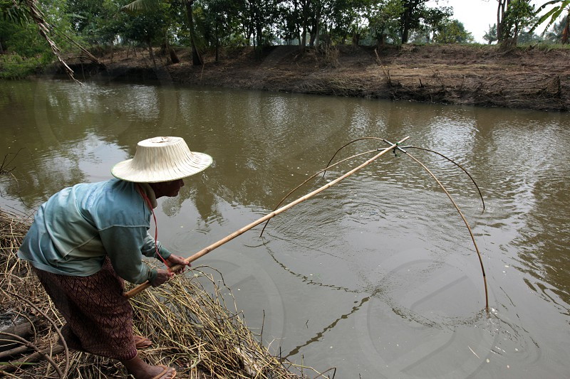 a women is fishing in a river near the city of Khorat in the Province of Nakhon Ratchasima in the Region of Isan in Northeast Thailand in Thailand. photo