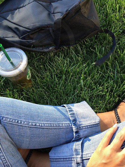A backpack a drink and a student on green grass.  photo