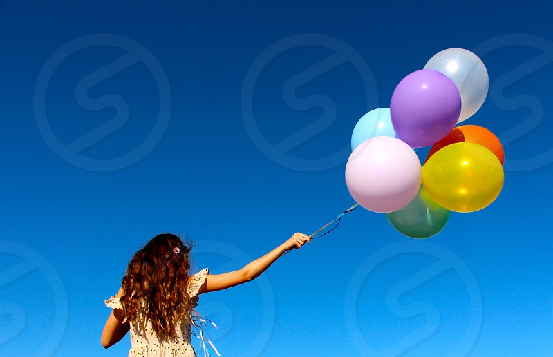 girl with long brown wavy hair wearing white sundress holding colorful balloons photo