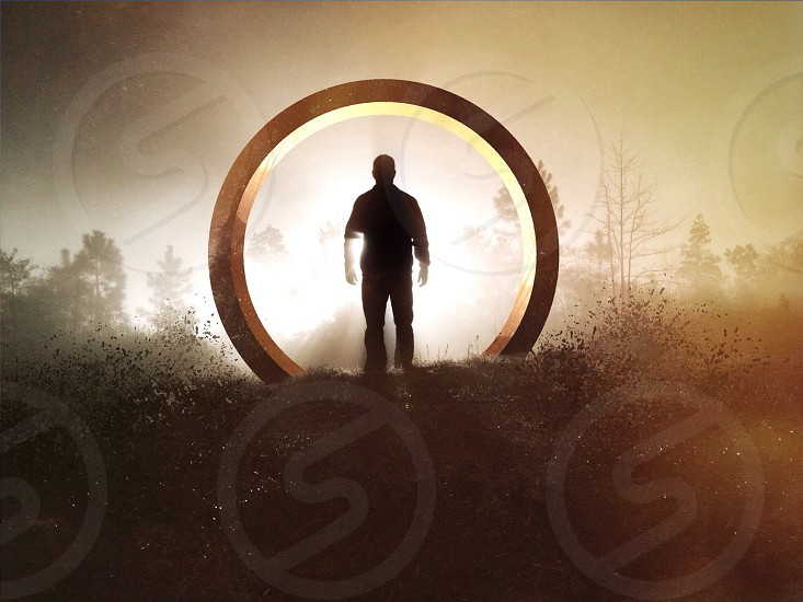 man's silhouette standing inside circle photo
