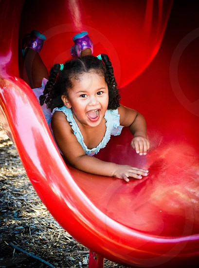 girl playing on red slide photo