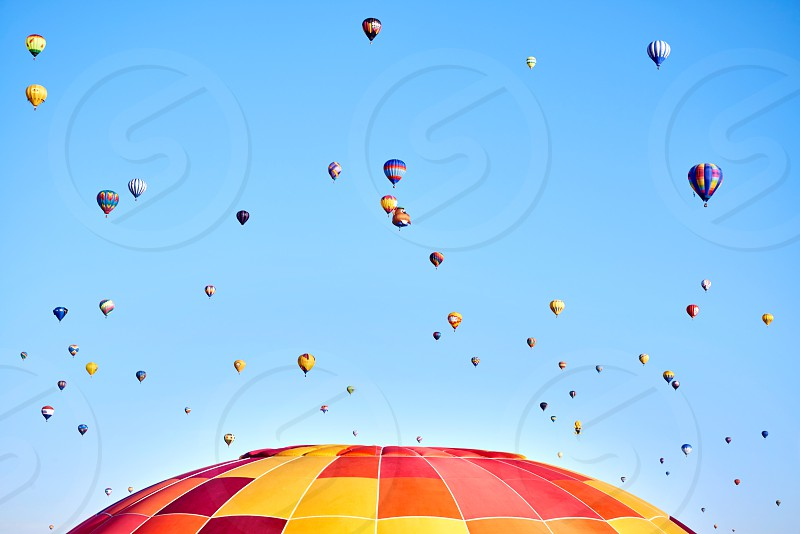 Hot air balloons rise in a mass ascension at the annual Albuquerque International Balloon Fiesta in Northern New Mexico.  photo