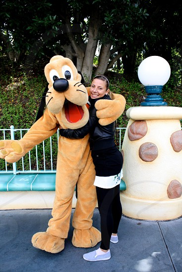 woman in black leather jacket hugging goofy mascot photo