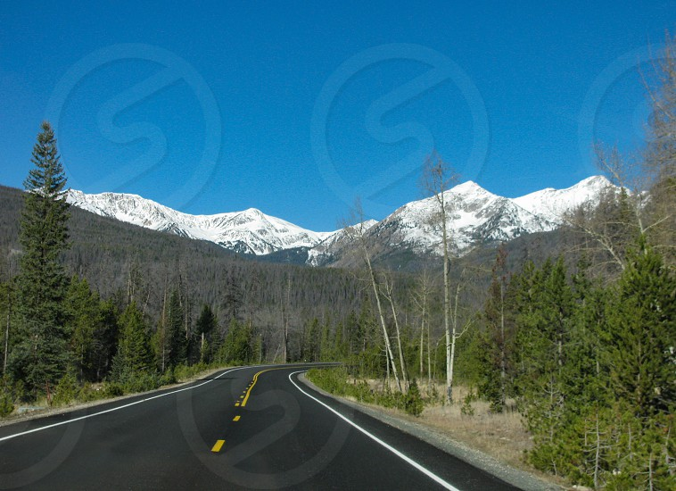 On the road again driving through Rocky Mountain National Park in Colorado in autumn with snow-capped mountains ahead beneath a clear blue sky. photo