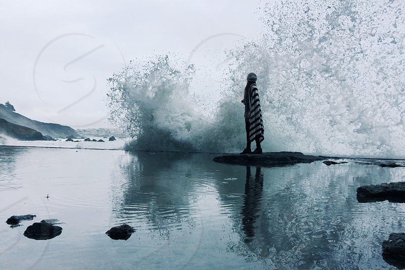 woman standing on rock with ocean wave photo