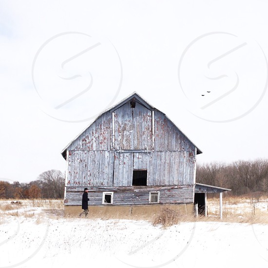 person standing by a grey wooden barn under blue sky during daytime photo