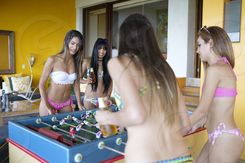 Four young attractive women in bikinis playing table football on outdoor terrace photo