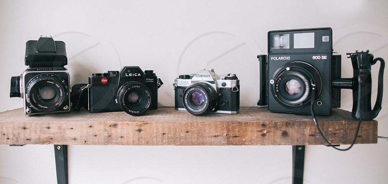4 classic cameras on brown wooden shelf photo