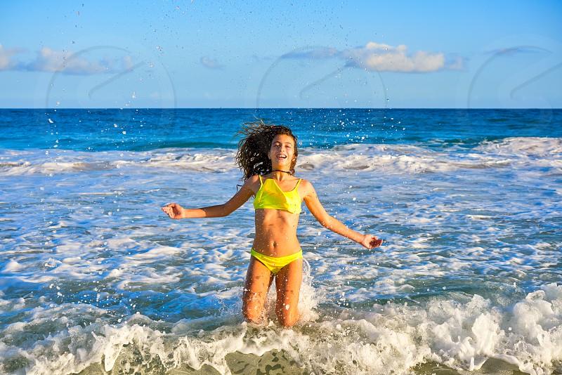 Bikini teen girl jumping happyt in Caribbean sunset beach splashing shore photo