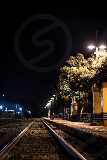 train tracks at empty station night time photo