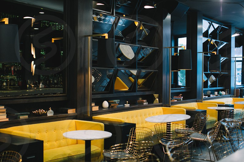 yellow tufted sofa in front of white round table and stainless steel chair and black wooden cubbyshelf in restaurant during daytime photo