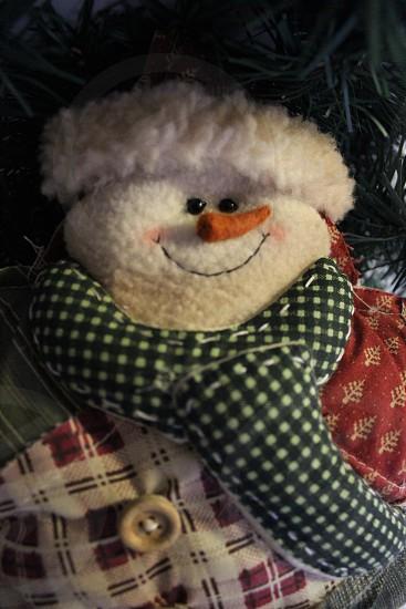 green scarfed snowman plush on tree photo
