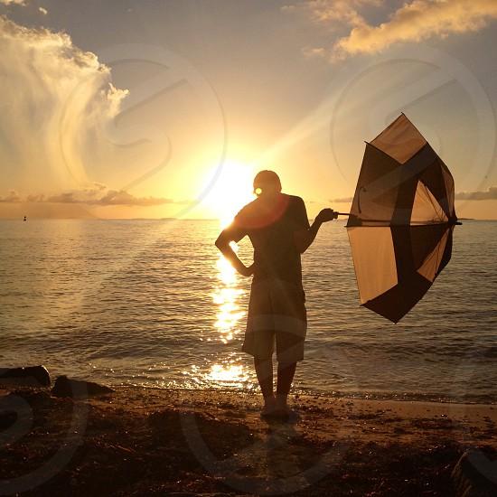man in beige shorts holding umbrella near sea photo