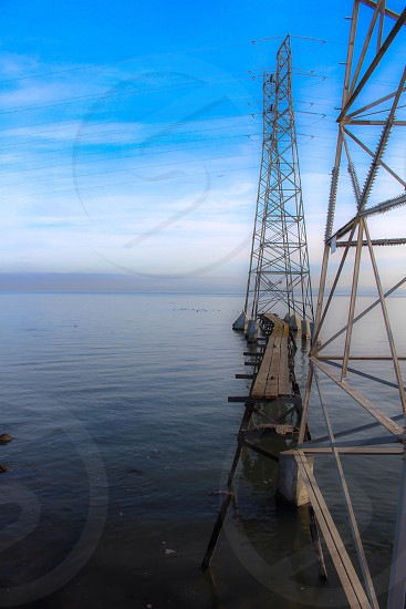 photo of grey transmission tower under clear blue sky photo