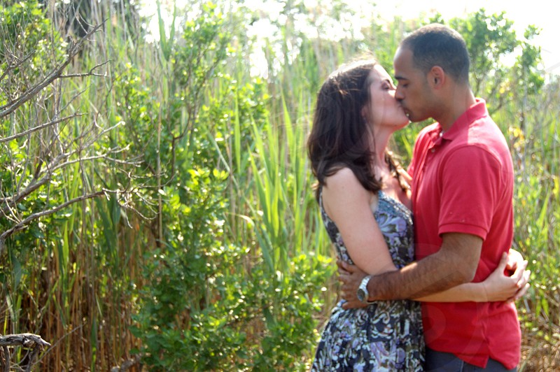 man in red polo shirt kissing woman photo