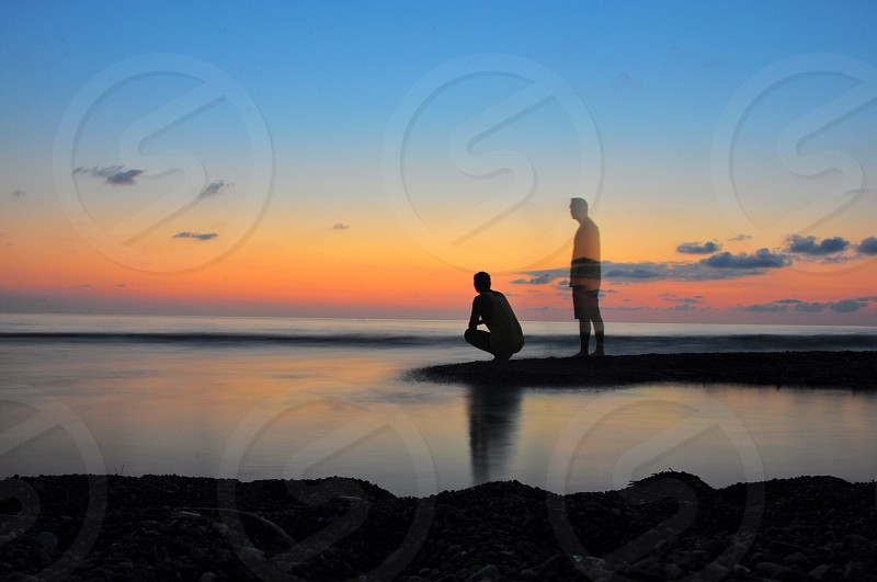 man sitting silhouette with faded man figure image photo