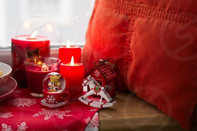 Christmas decoration: candies toyspillow and burning red candles on windowsill photo