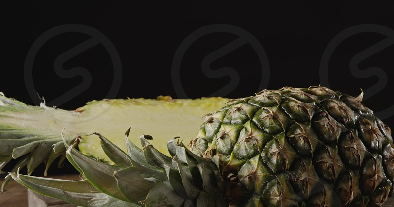 Close-up fresh organic tropical fruit pineapple on a cutting board on a wooden table on a black background. Dolly slow motion 4K UHD video 3840 2160p. Concept of vegetarian diet eating. photo