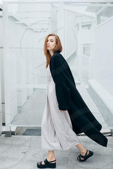woman in black fleece coat walking along hallway photo
