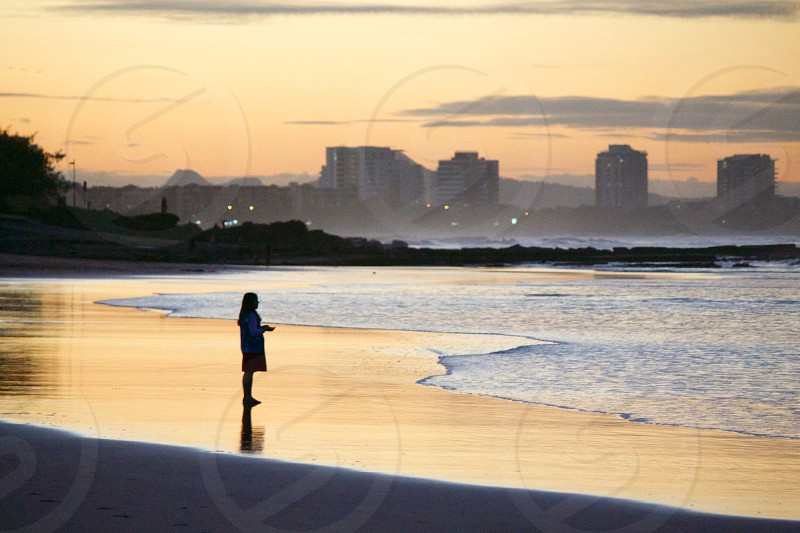 City surf sunset glow girl buildings lights sand quiet lone photo