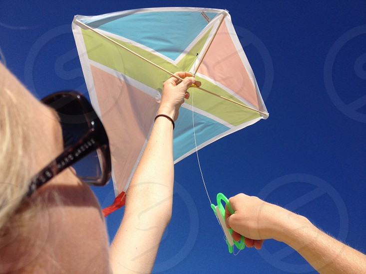 woman holding a blue pink and yellow kite photo