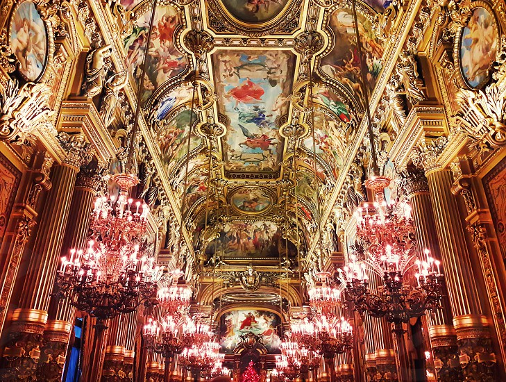 Interior of Opera Garnier Palace and a golden painted ceiling with a lot of chandeliers hangining in Paris France. photo