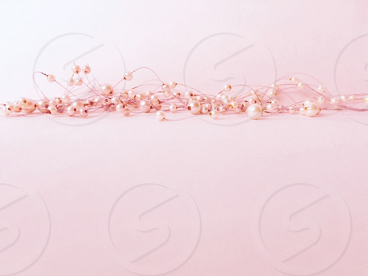Low angle view of light-coral-colored faux pearls against a light coral background  photo