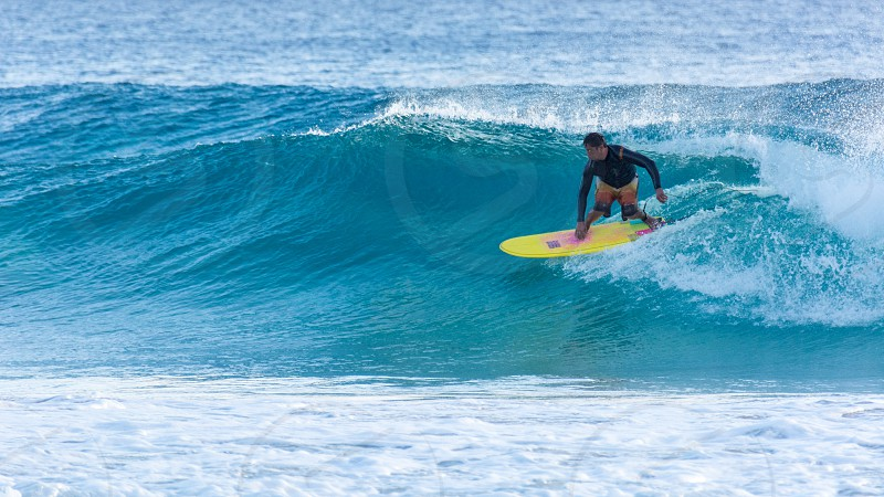 surfer surfing blue water wave spray clean yellow board surfboard tropical clear photo