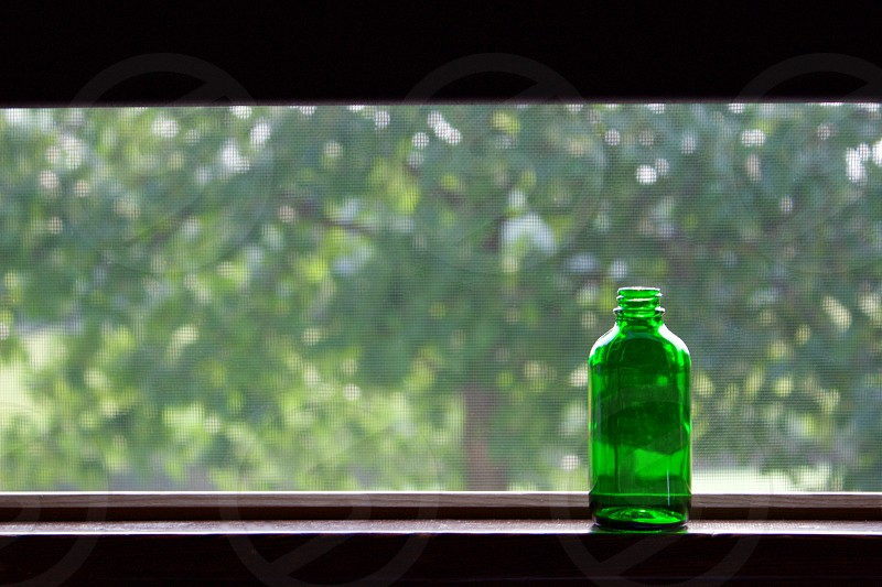 A small empty green bottle on a windowsill by an open screened window and a dark brown shade partially pulled down with a blurred tree visible in the background photo