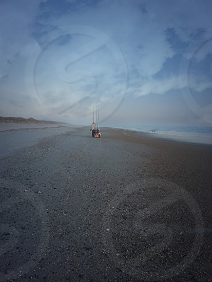 Lone Fisherman pulls fishing cart loaded with gear on deserted beach at early morning. photo